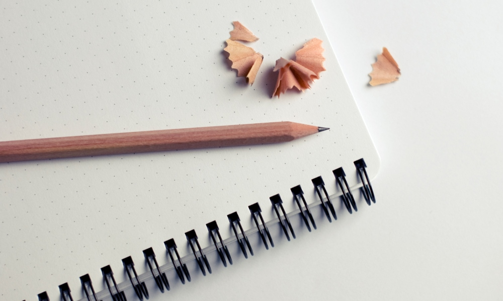 sharpened pencil on top of a notebook